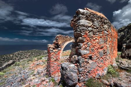 Abstract ruins of abandoned old temple Crete island. Greece. Stone construction under dark sky. Dramatic view of ancient landmark. Apocalyptic and evil concept, fairly tale mysterious background