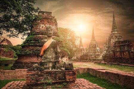 Asian religious architecture. Ancient sandstone sculpture of Buddha at Wat Phra Sri Sanphet  temple ruins under sunset sky. Ayutthaya, Thailand travel landscape and destinations Zdjęcie Seryjne