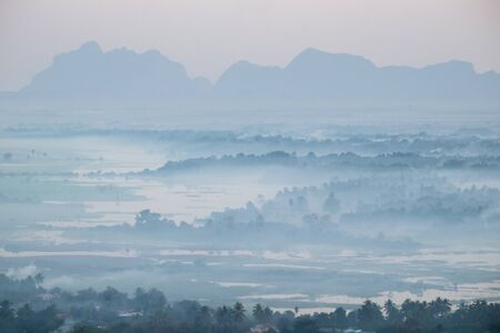 Amazing watercolor view of foggy morning landscape with farm fields at Thanlwin river. Hpa An, Myanmar (Burma) travel landscapes and destinations Zdjęcie Seryjne