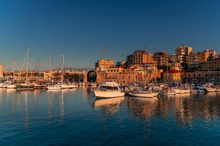 Panoramic view of beautiful sunset in Koules Fortress (Rocca a Mare), Crete island. Yachts reflecting in the mirror of water near Venetian old harbor in Heraklion city. Amazing destination in Greece