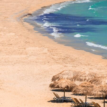 Abstract view of amazing beach landscape with straw umbrella near azure sea. Mediterranean paradise in Greece. Travel background and destinations