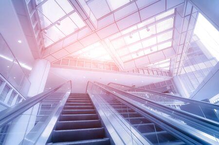 Escalator in modern business center. Blue toning image