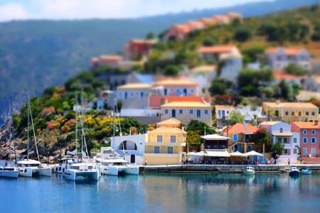 Soft focus and tilt shift  blur.  Colorful Asos village at Kefalonia island. Greece. Popular destination on Ionian Sea for vacation. Mediterranean port for traveling by yacht and honeymoon paradise Zdjęcie Seryjne
