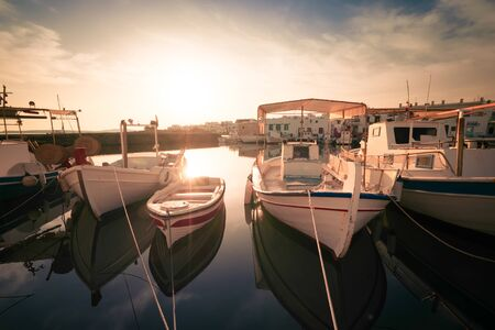 Panoramic view of Paros island popular tourist attraction, Naousa town. Promenade zone along port with restaurants and shops. Harbor of Aegean Sea, boats and yachts in quay at sunset. Greece Zdjęcie Seryjne