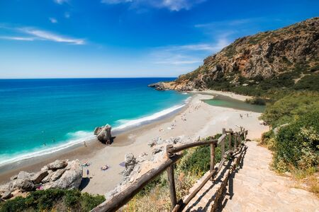 Amazing Preveli beach with turquoise water and rocky hills. People swimming in azure water and sunbathing on sand. Tourists relaxing on Crete on sunny day. Picturesque seascape and skyline, Greece