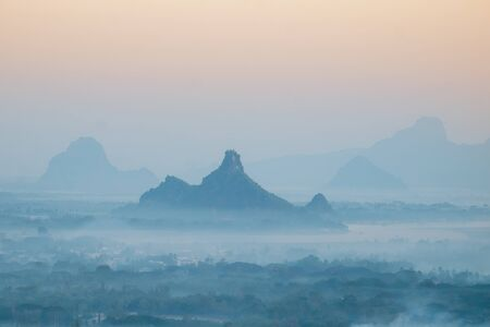 Amazing watercolor view of foggy morning landscape with farm fields and Phar Pu mountain at Thanlwin river. Hpa An, Myanmar (Burma) travel landscapes and destinations