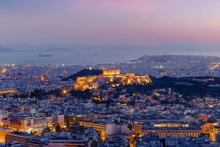Amazing aerial view of Athens, Greece. Night over ancient Acropolis, ruins. Parthenon, the Icon of the hellenic civilization, Aegean sea on background. Traditional mediterranean architecture