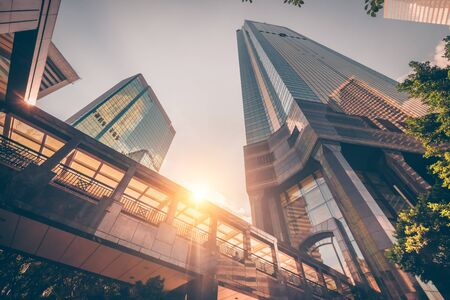 Abstract futuristic cityscape view with modern skyscrapers. Sun shines in the sunset sky, reflecting in glass of the footbridge. Urban architecture background. Hong Kong