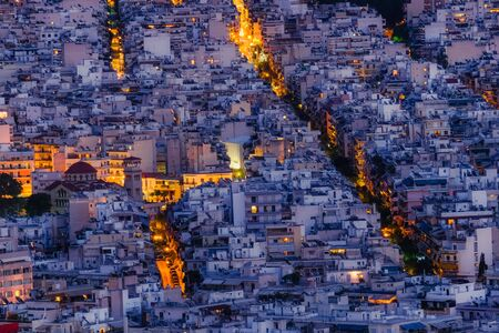 Amazing aerial night view of Athens cityscape. Traditional white houses at evening. Greece capital and famous ancient mediterranean town.