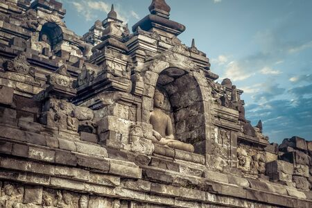 Amazing carved statue of Buddha sitting in meditation position against blue sky on background. Ancient Borobudur Buddhist temple. Great religious architecture. Magelang, Central Java, Indonesia
