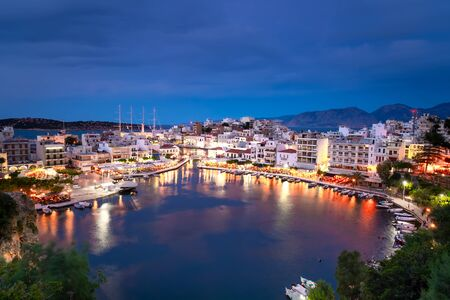 Beautiful sunset at Agios Nikolaos city, Port at Aegean sea. Crete,Greece. Peaceful harbor of Voulismeni Lake. Long promenade with restaurants.  Panoramic view of seaport with yachts and boats at quay Zdjęcie Seryjne