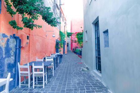Cafe and restaurants at amazing narrow streets of popular destination on Crete island. Greece. Traditional architecture and colors of mediterranean city. Place for romantic vacation and summer travel Zdjęcie Seryjne