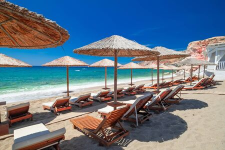 Amazing sandy beach landscape with chairs for relaxation and umbrellas on sunny day. Milos island on Aegean sea. Greece. Vacation in paradise concept