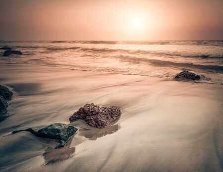 Sunset at tropical beach. Rocks at the ocean coast under evening sun. South India  landscape