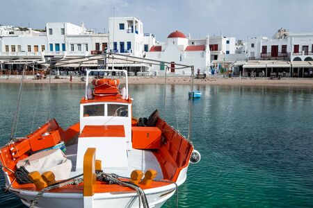 Mykonos town panorama with Greek Orthodox church. Traditional white buildings on embankment and boats on quay. Harbor of Aegean sea, Mykonos island. People walking on bay, Greece