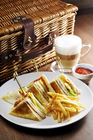 Club sandwich,  french fries  and cappuccino. With a smooth taste.