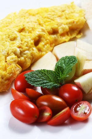 Healthy Low fat breakfast has Vegetable omelet and fruit.