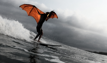 scary man: Scary human size bat man surfing a wave