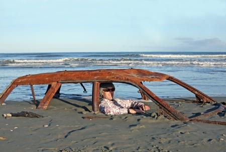 男はビーチで砂に埋もれて錆びた車の大破で座っています。