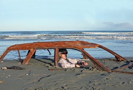 Man sits in rusted car wreck buried in sand on Beach