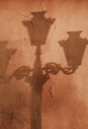 Shadow of old street lamp post on wall