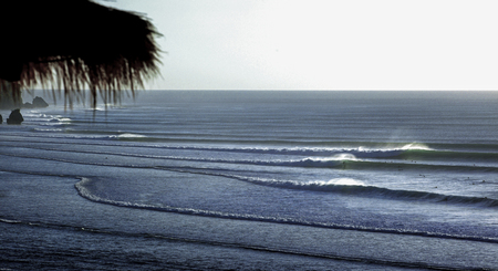 Surfers riding waves on the Bukit Peninsula surfing coastline in Bali Фото со стока