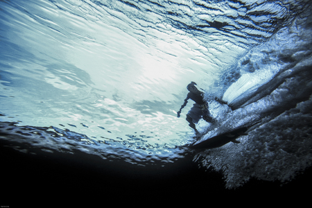 Underwater view of surfer riding wave Фото со стока