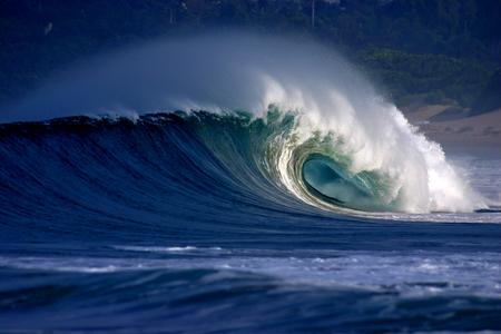 Tubular surfing wave breaking onto tropical beach Фото со стока