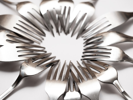 tine: Detail of many forks on a white table