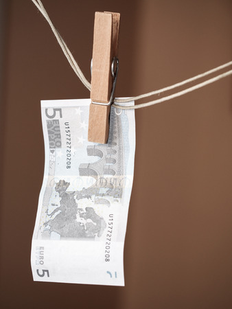 A five euro note and a clothespin as a symbol of money laundering photo