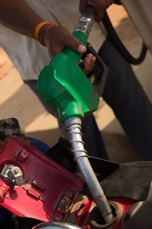 Person filling the Petrol using oil dispenser to bike petrol tank close up.