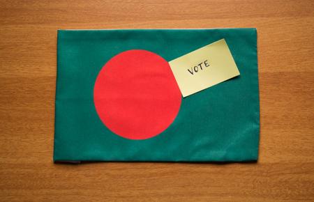 Voting concept - Hand Written Voting Sticker on Bangladesh Flag.