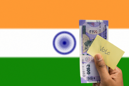 Hand holding money and vote a concept of political corruption the purchase of votes in elections background as a Indian flag 版權商用圖片