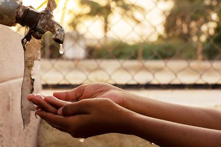 Close-up van handen, kind drinkwater rechtstreeks uit kraanwater van het bedrijf in India. Stockfoto