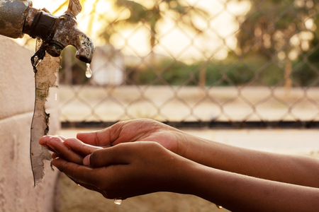 Closeup of hands, child drinking water directly from corporation tap water in India. Standard-Bild