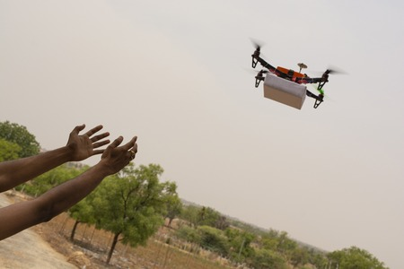 Assembled Drone quadcopter delivering a package and hands receiving the parcel