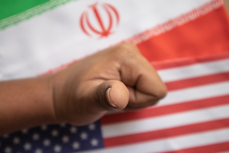 Concept of bilateral relations of US and Iran deal showing with flag and hands showing of deal gesture.
