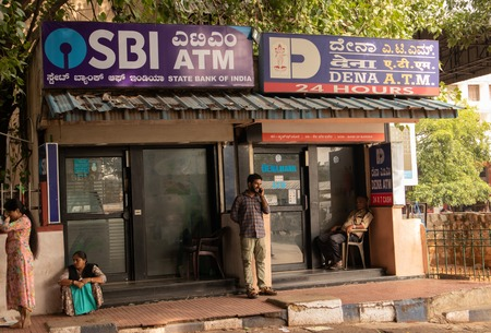 BANGALORE INDIA June 3, 2019 :People sitting infront of the SBI ATM and DENA bank ATMs at bangalore railway station