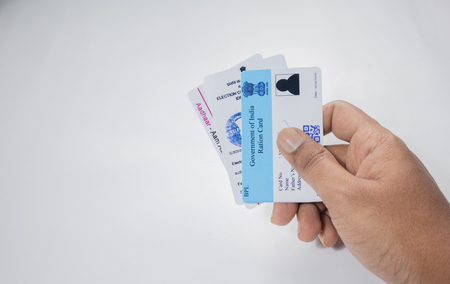 Maski,Karnataka,India -June 26 ,2019: Holding Aadhaar card, Ration card and voter ID which is issued by Government of India as an identity card on isolated background. Banque d'images - 125989549