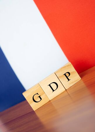 Gross Domestic Product or GDP of France in wooden block letters on table, France flag as a background 写真素材