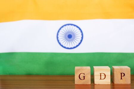 GDP or gross domestic product in wooden block letters, Indian Flag as a background Stock Photo