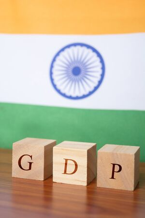 GDP or gross domestic product in wooden block letters, Indian Flag as a background 写真素材