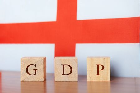 GDP or gross domestic product of England in wooden block letters, England Flag as a background