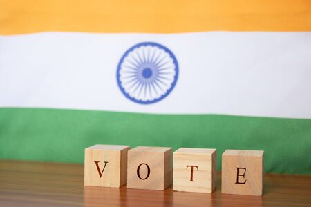 Concept of Indian Election, Vote in wooden letters on table, Indian Flalg as a background