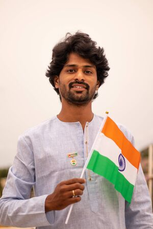 Portrait of a Young Indian man holding Indian flag in traditional Indian dress.