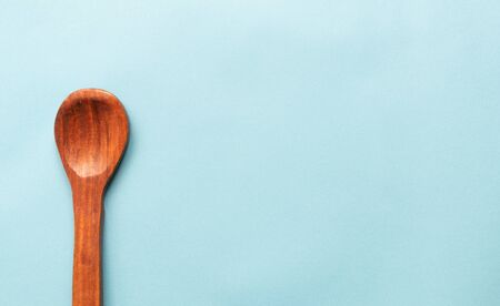 Concept of Minimalism showing with Single Wooden spoon on blue colored background. Фото со стока