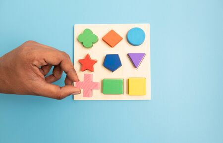 Top view Hands Picking up one Colorful Wooden building blocks in different shapes on blue background