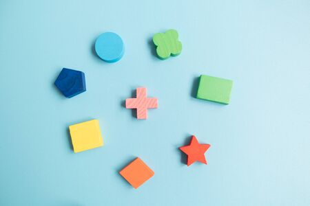 Top view Colorful Wooden building blocks with different shapes for developing and entertainment of Children on blue background