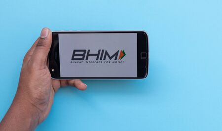 Maski, India 25, August 2019 :Hands using BHIM or Bharat Interface for Money app is a digital wallet by Indian Government loading on mobile phone