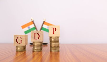 GDP or gross domestic product in wooden block letters on Coins in Increasing order with Indian flag as a background Zdjęcie Seryjne
